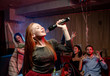 Leinwanddruck Bild - young caucasian woman with red hair sing in karaoke bar, wearing party clothes, have good voice to sing, emotional and energetic woman