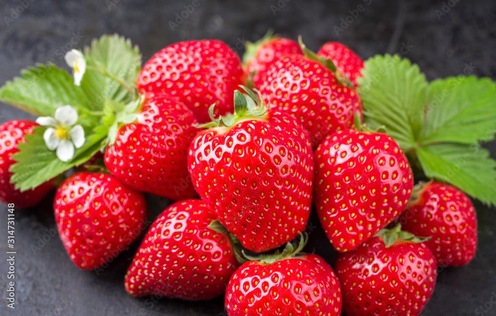 Fototapeta Fresh ripe strawberries offered as closeup on black rustic board as background