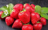 Fototapeta Kawa jest smaczna - Fresh ripe strawberries offered as closeup on black rustic board as background