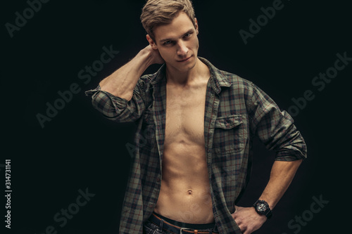 obraz dibond Portrait of a beautiful young athletic man in checkered shirt with opened naked torso in the studio, black background. Caucasian man looking side