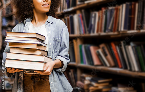 Obraz Photo for background, place for insertion, African American woman student holding a heavy armful of books in her hands against the background of bookshelves in a library. Learning concept, lifestyle - fototapety do salonu
