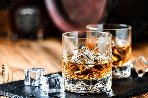 Photo Glass of whiskey with ice cubes on black stone table