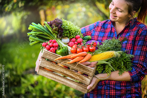 Farmer woman holding wooden box full of fresh raw vegetables Fototapete