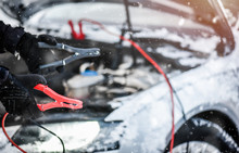 Hands Charging Car Battery With Electricity Trough Electric Cables. Vehicle Jumper Cable Cars Starting Or Connection In Winter Time.