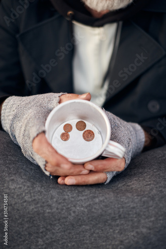 Homeless man's hands holding half empty mug with some coins at bottom Canvas Print