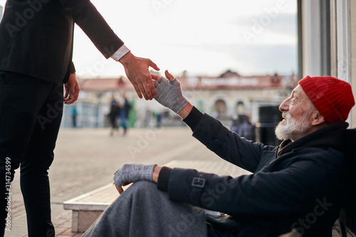 Senior beggar sitting beside street with request help with receive some coins from kind business man Wallpaper Mural