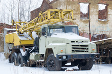Old Broken Truck Crane With A Yellow Arrow And A White Cab. Winter.