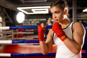 Tactical efficiency of young fit caucasian woman in ring, training, boxing in sportive wear. Professional fighter, female boxer in red protective gloves