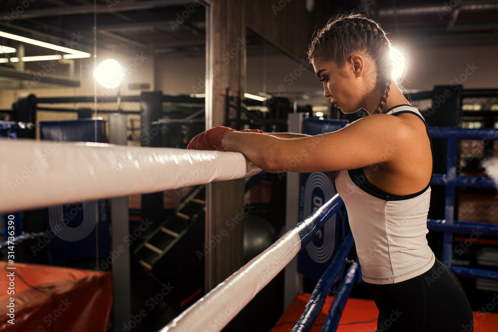 Fototapeta tired caucasian woman boxer stand leaning on the fence, after successful training in the ring. Sport concept