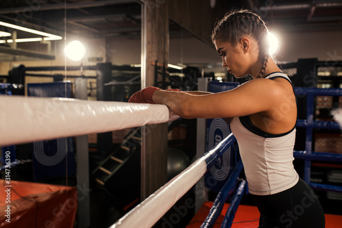 Fototapeta tired caucasian woman boxer stand leaning on the fence, after successful training in the ring. Sport concept obraz