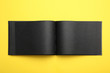 canvas print picture - Stylish open black notebook on yellow background, top view