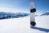 Snowboard Standing In Snow With Winter Mountains In Background