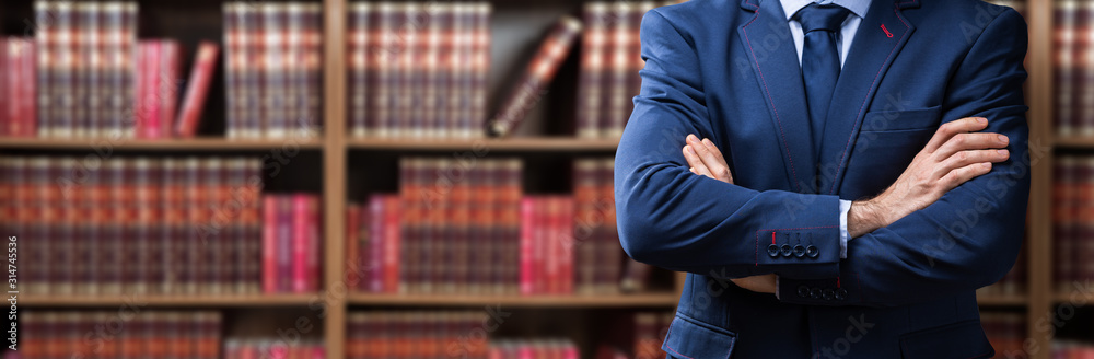 Fototapeta Midsection Of Lawyer Standing Against Bookshelf