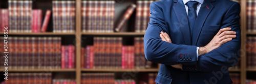 Midsection Of Lawyer Standing Against Bookshelf - 314745536