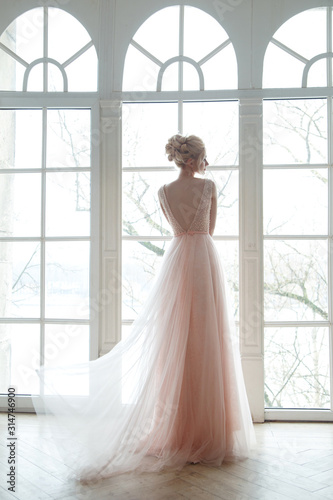 Photo Silhouette of a chewing gum bride in an airy powdery dress on a window background