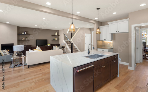 Kitchen And Living Room In New Luxury Home Kitchen Features Waterfall Island With Large Sink Open Concept Floorplan Shows Living Room Stairs And Fireplace With Fire Stock Photo Adobe Stock