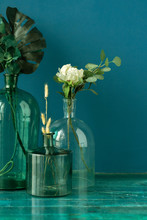 Artificial Flowers And Dry Plants In Transparent Bottle Vases On The Floor Against Blue Wall. Fine Art Still Life Flowers Concept