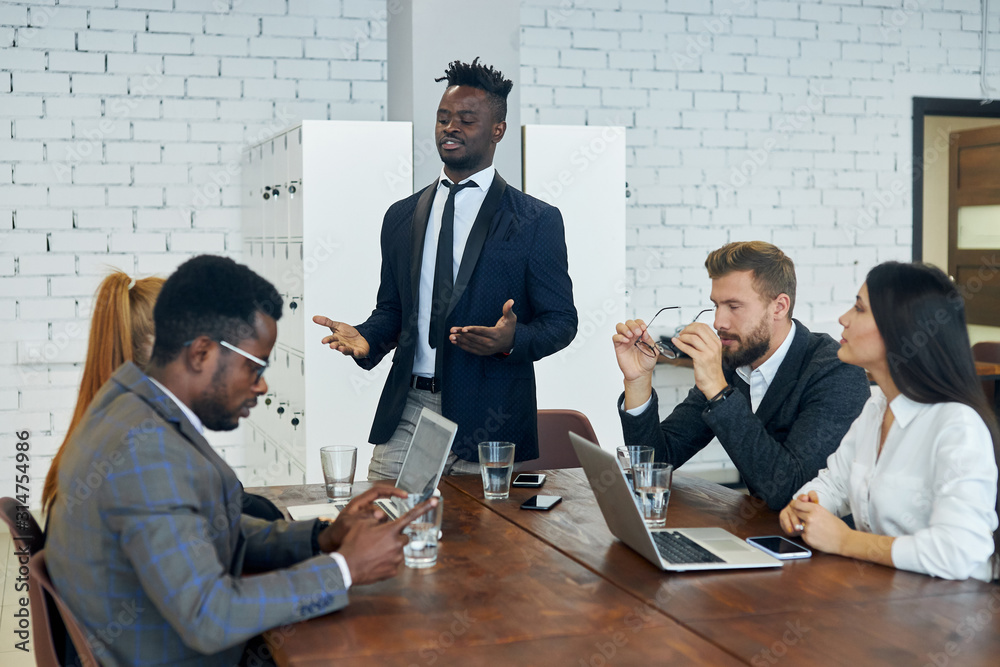 Fototapeta Personable black employee explains to foreign colleagues new client management strategy idea at modern group office training