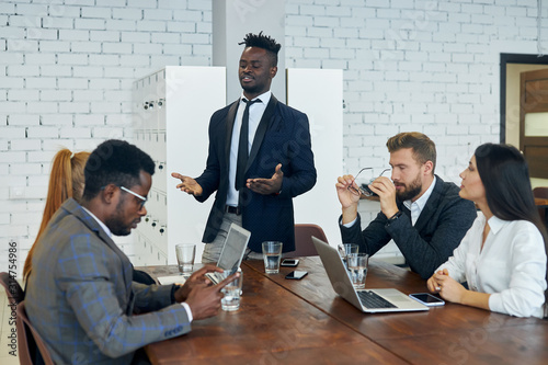 Personable black employee explains to foreign colleagues new client management s Fototapete