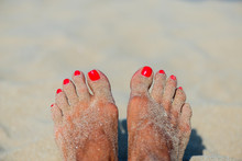 Summer Vacation Concept  Female Bare Feet With Red Lacquer On Sand Background  - Selective Focus, Copy Space