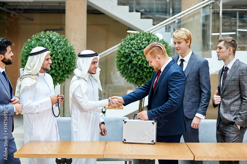 Confident businessmen from dubai and america shaking hands to each other Wallpaper Mural