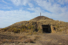 Underground Dwelling. Photography Of A Hut In The Ground With A Protruding Pipe. The House Of The Ancient Man