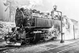 Historische Aufnahme einer alten Dampflok an einem Bahnsteig