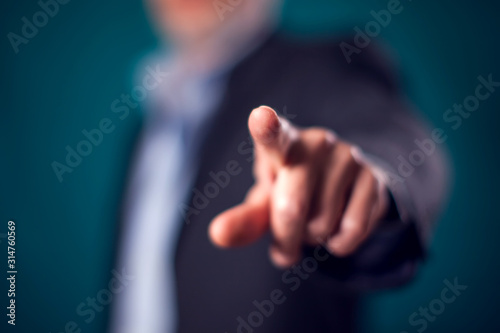 Obraz Businessman in suit point finger at camera in front of black background - fototapety do salonu