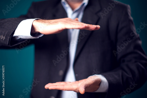 Businessman in suit showing something invisible in hands in front of black background