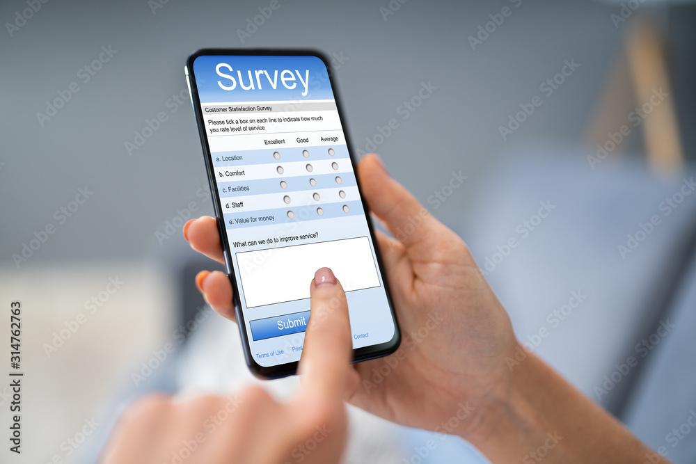 Fototapeta Person Filling Survey Form On Mobile Phone