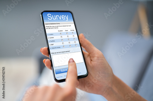 Person Filling Survey Form On Mobile Phone
