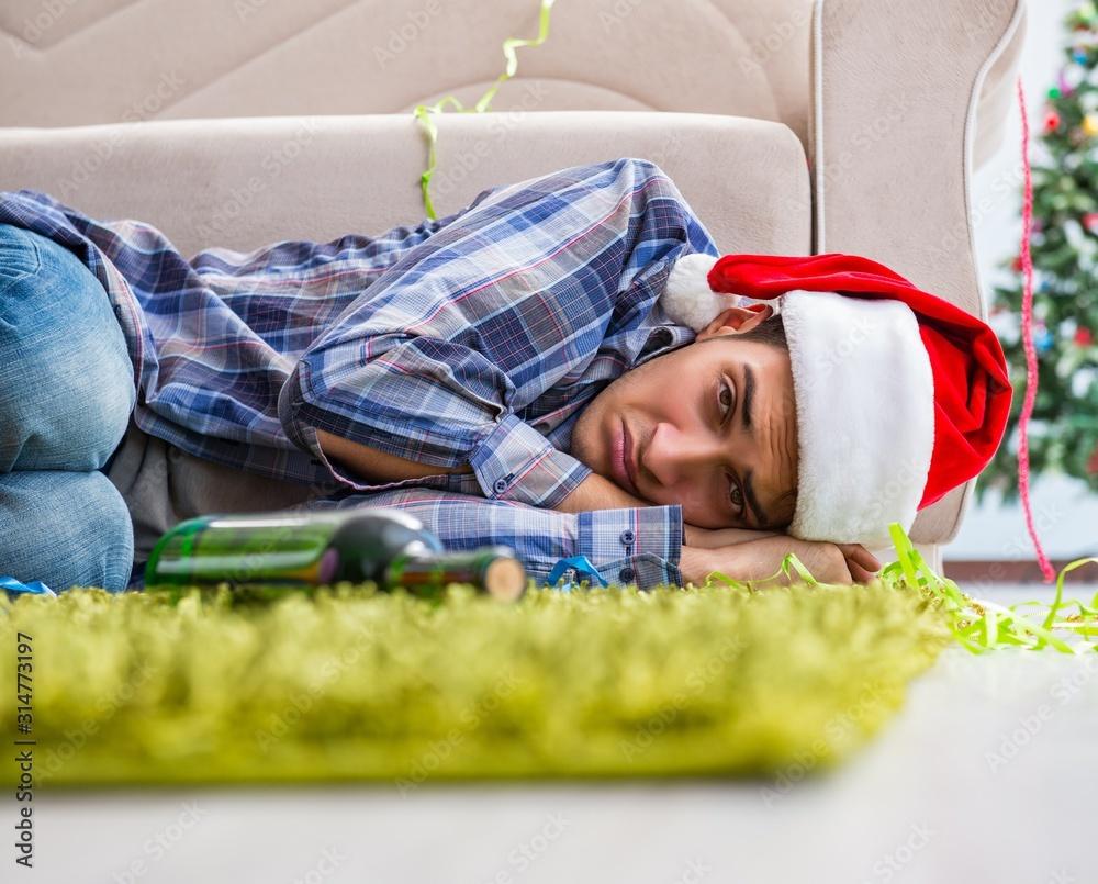Fototapeta Man having hangover after christmas party