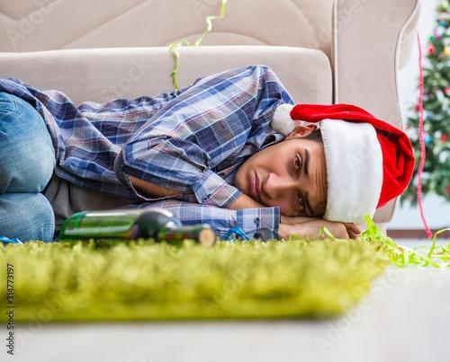 Obraz Man having hangover after christmas party - fototapety do salonu