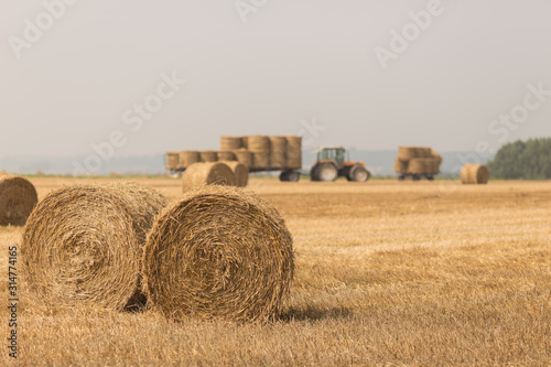 Valokuvatapetti Tractor working in a field with bales of hay