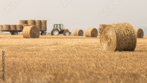 Tractor working in a field with bales of hay Canvas Print