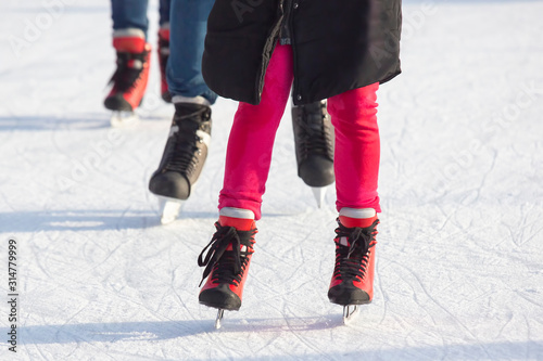 different people are actively skating on an ice rink Fototapet