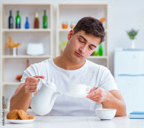 Man falling asleep during his breakfast after overtime work Canvas Print