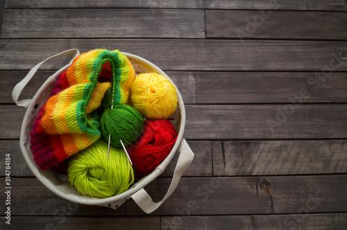 Obraz Yarn for knitting rainbow. Wood background. - fototapety do salonu