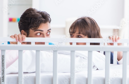 Photo Happy young family at baby bed cot