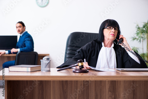 Fototapeta  Young intern asking senior judge for advice