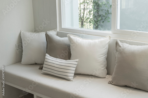 Obraz Corner of stylish living room with white walls, wooden floor, comfortable gray sofa with cushions near window - fototapety do salonu