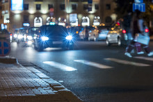 City At Night. Car Traffic With Lights On During Rush Hour. Out Of Focus Picture