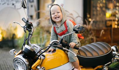 Small happy baby in a bodysuit sits on a motorcycle and experiences an emotion of joy. Motorcycle advertising.