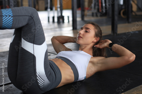 Fototapety, obrazy: Image of young woman in sportswear doing crunches at the gym.