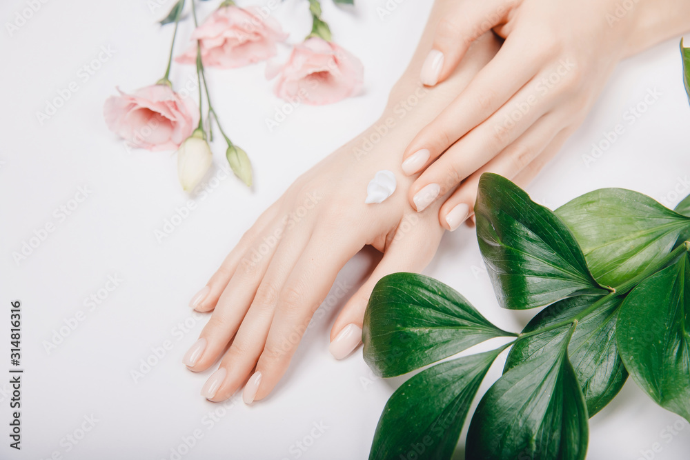 Fototapeta Top view cosmetic cream on female hands with pink flowers on white background, flat lay. Concept spa skin care