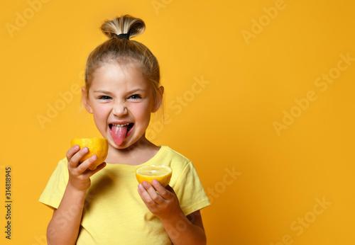 Obraz na płótnie Little smiling cute girl in yellow t-shirt holding halves of fresh sour ripe lem