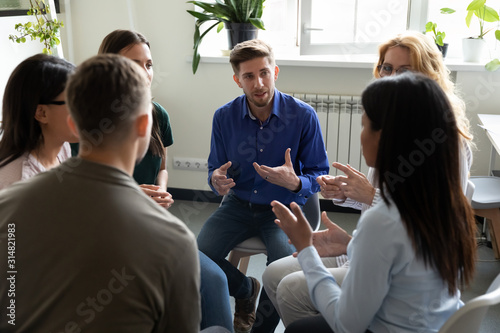 Diverse people seated in circle participating at group therapy session - 314821983