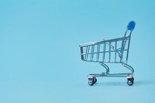 Shopping Trolley On Blue Background With Some Copy Space