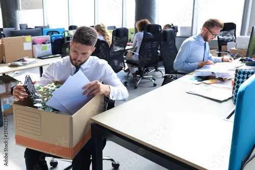 Sad dismissed worker are taking his office supplies with him from office Tablou Canvas