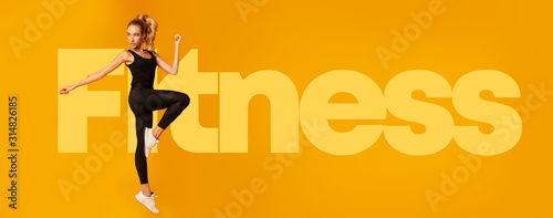 Fotomural  Fit Woman Jumping In Studio Over Fitness Lettering